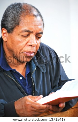 African american male reading his bible in church. - stock photo
