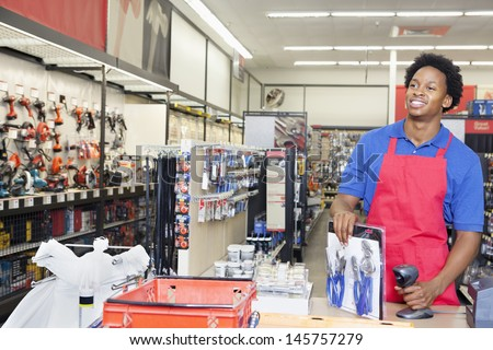 African American male store clerk at checkout counter in super market - stock photo