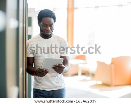 African American male student using digital tablet at library - stock photo