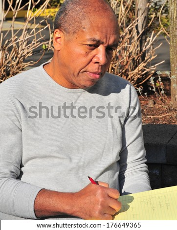 African american male writing his thoughts outside.