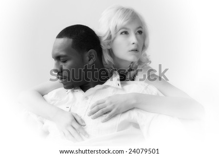 African American man and Caucasian woman holding each other. Naturally lit, high-key image on white background.