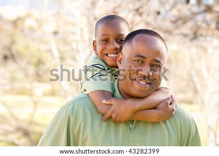 African American Man and Child Having Fun in the Park. - stock photo