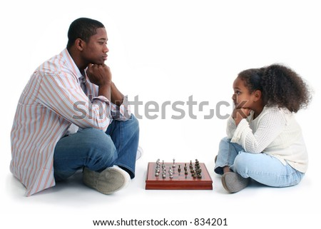 African American man and little girl playing chess.  Sitting crossed-legged on either side of game and looking at each other.  Shot in studio over white. - stock photo
