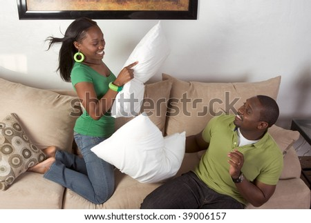 African-American man and woman fooling around engaged in pillow fight - stock photo