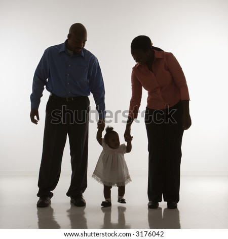 African American man and woman standing holding up infant girl by her hands against white background.
