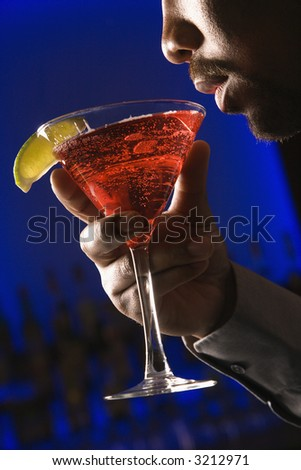 African American man bringing martini up to lips in bar against glowing blue background.