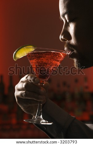 African American man drinking martini in bar against glowing red background.