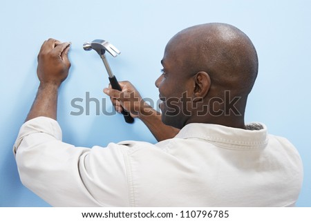 African American man hammering nail into blue wall - stock photo
