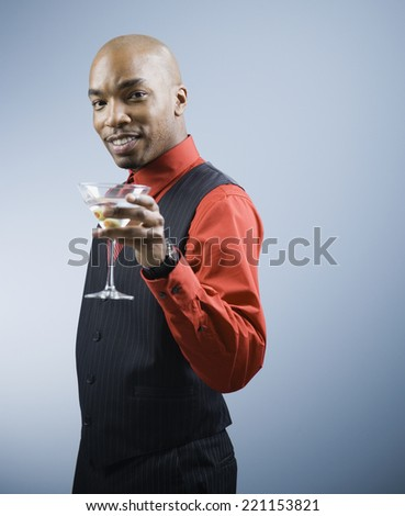 African American man holding cocktail - stock photo