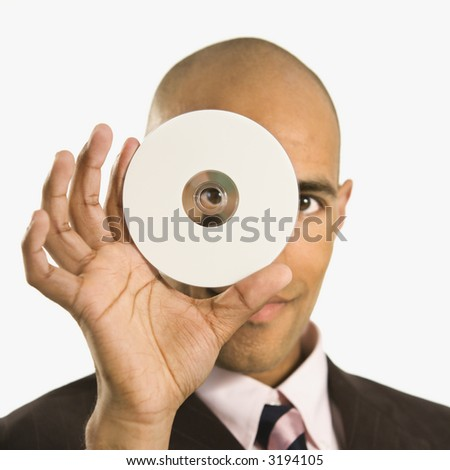 African American man holding compact disc over face and peeking through hole. - stock photo