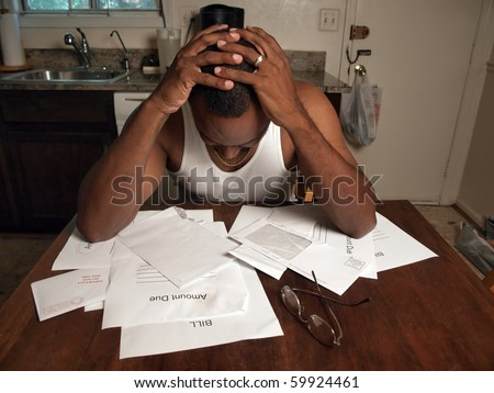 african american man holding his head as if under stress of his financial debt - stock photo
