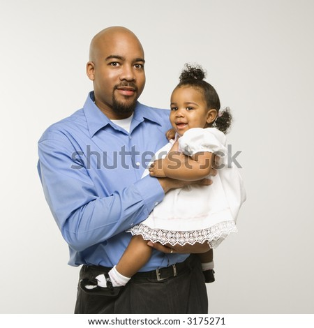 African American man holding infant girl standing against white background. - stock photo