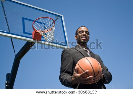 African American man in a business suit posing with a basketball.  He could be a coach player recruiter or trainer. - stock photo