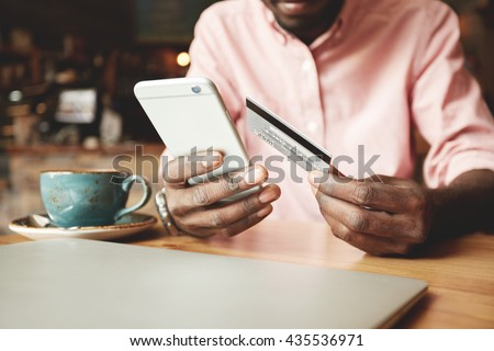 African American man in casual shirt paying with credit card online while making orders via the Internet. Successful black businessman making transaction using mobile bank application. Selective focus - stock photo