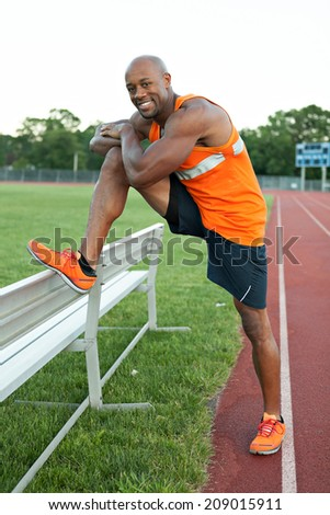 African American man in his 30s stretching out before a run at a sports track outdoors. - stock photo