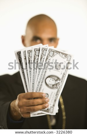 African American man in suit holding cash. - stock photo