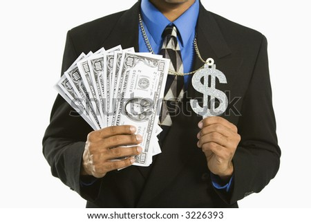 African American man in suit wearing necklace with money sign and holding cash. - stock photo