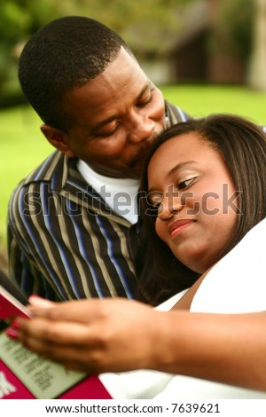 african american man kissing his wife who reading a book. focus on the woman - stock photo