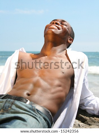 African American Man Laughing While Posing Outdoors at the Beach - stock photo