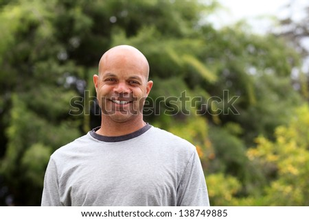 African american man poses outside in the park