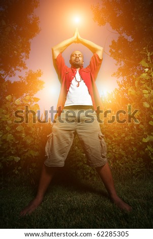 African American man practicing yoga outdoors - stock photo