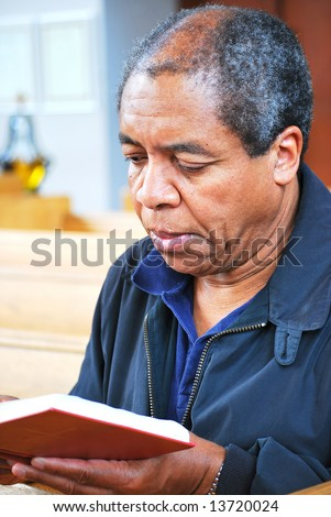 African American man reading his bible in church. - stock photo