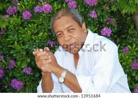 African american man sitting in a flower garden. - stock photo