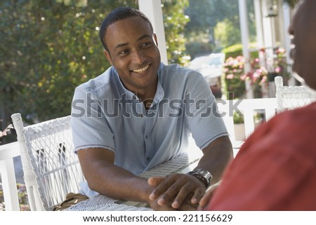 African American man sitting on porch - stock photo