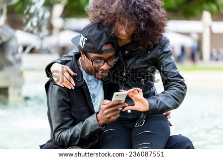 African American man sitting with girlfriend at fountain showing message on mobile phone or looking up information  - stock photo