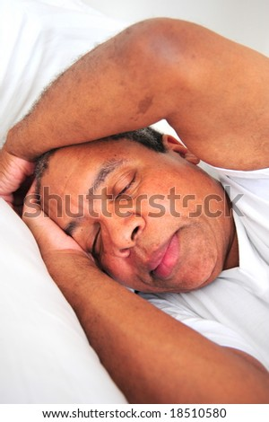 African American man sleeping in bed.