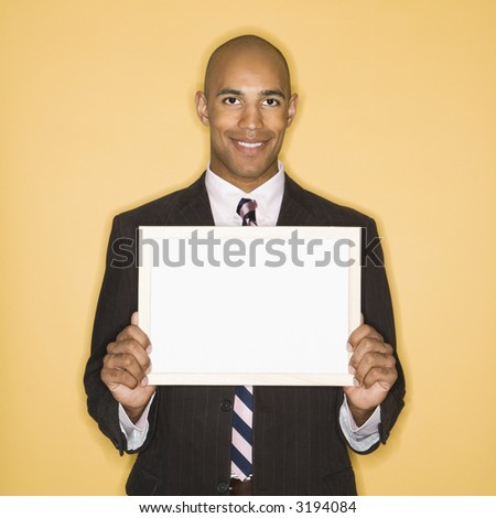 African American man smiling holding blank sign against yellow background. - stock photo