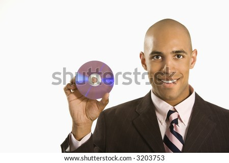 African American man smiling holding out compact disc. - stock photo