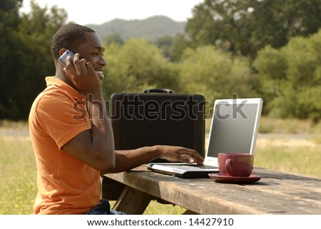 African American man speaking on the phone while working on laptop computer