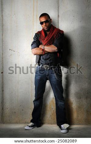 African American man standing in front of grunge wall