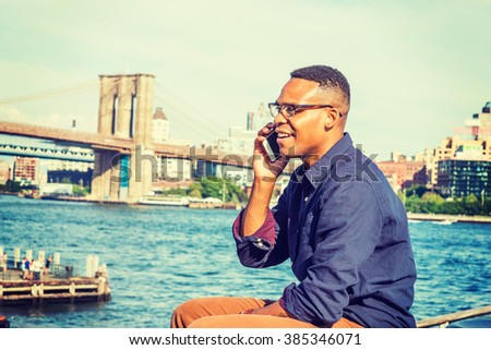 African American Man traveling, working in New York. Wearing blue shirt, brown pants, glasses, a college student sitting by East River, smiling, talking on phone. Brooklyn bridge on background.  - stock photo