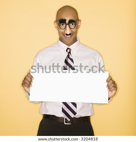 African American man wearing groucho mask disguise holding blank sign. - stock photo