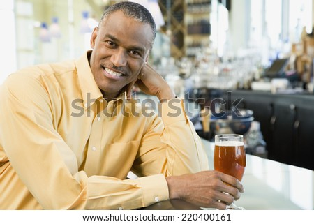 African American man with drink at bar - stock photo