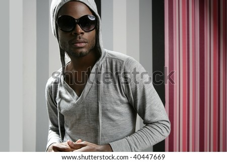 African american man with gray hood over wallpaper background