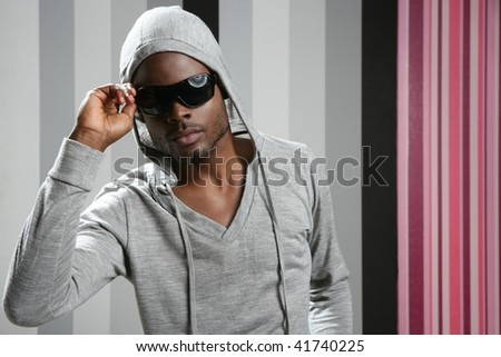 African american man with gray hood over wallpaper background - stock photo