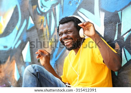 African American man with headphones on graffiti wall background