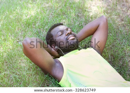 African American man with headphones over green grass in park