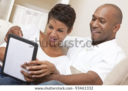 African American Man Woman Couple Using Tablet Computer - stock photo