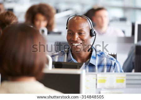 African American man working at a computer in a call centre - stock photo