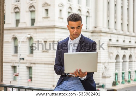 African American man working in New York. Wearing black blazer, college student sitting on railing by vintage office building on campus, reading, studying on laptop computer.