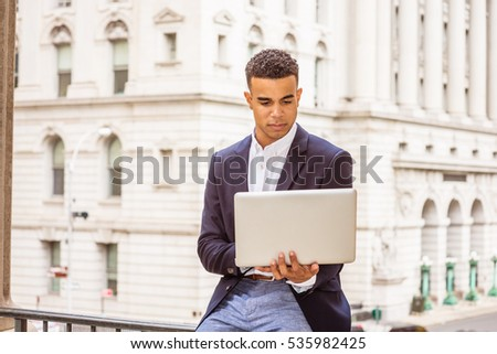 African American man working in New York. Wearing black blazer, college student sitting on railing by vintage office building on campus, reading, studying on laptop computer. Color filtered effect.