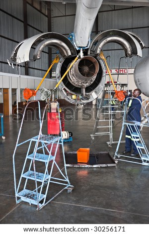 african american man working on the jet engine, aircraft maintenance, dismantled plane engine - stock photo