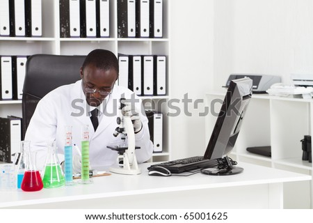 african american medical scientist wearing lab coat with microscope and test tubes in laboratory - stock photo