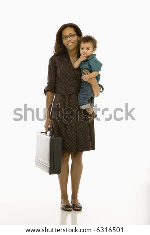 African American mid adult businesswoman holding toddler son on hip smiling at viewer. - stock photo