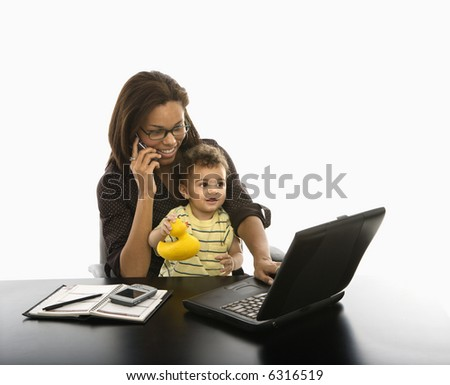 African American mid adult businesswoman working on laptop and cell phone with toddler son on lap.