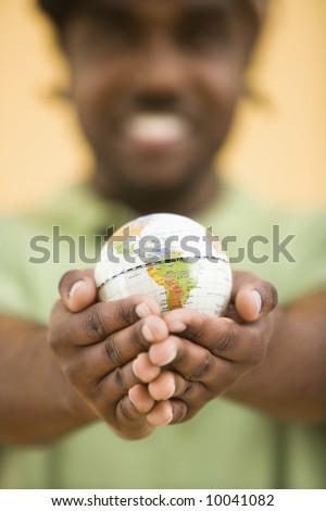 African-American mid-adult man wearing hat holding small globe toviewer. - stock photo